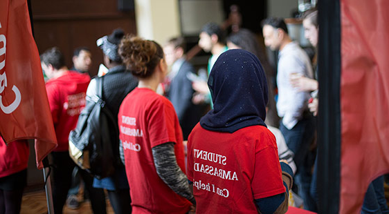 Two student ambassadors watch a crowd at an offer holder event